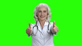 Lycklig kvinnadoktor som ger upp två tummar stock video