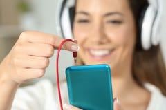 Lycklig kvinnahand som pluggar stålarkontaktdonet för att ringa Arkivfoton