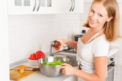 Lycklig kvinnahemmafru som förbereder sallad i kök Fotografering för Bildbyråer