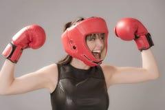 Lycklig kvinnakämpe som bär en huvudgavel och röda boxninghandskar royaltyfri foto