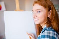 Lycklig kvinnakonstnärdanande skissar på kanfas i konstgrupp Arkivbild