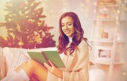 Lycklig kvinnaläsebok hemma för jul Arkivfoto