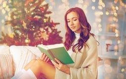 Lycklig kvinnaläsebok hemma för jul Royaltyfria Foton