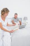 Lycklig kvinnaläsebok, medan maken använder bärbara datorn Arkivbild