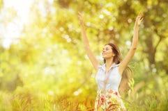 Lycklig kvinnalivstil som ler flicka lyftta öppna armar som är utomhus- arkivfoton