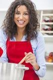 Lycklig kvinnamatlagning i kök Arkivfoto