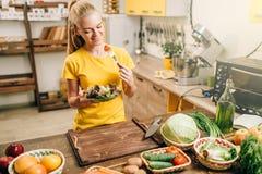Lycklig kvinnamatlagningsallad, bio mat som förbereder sig arkivfoton