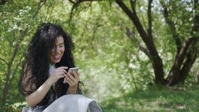 Lycklig kvinnamessaging med vänner som använder hennes telefon och kopplar av i trädgård stock video