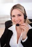 Lycklig kvinnaoperatör med hörlurar med mikrofon Royaltyfri Foto