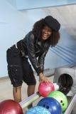 Lycklig kvinnaplockning upp en bowlingklot Royaltyfri Bild
