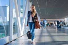 Lycklig kvinnaresande och gå i flygplats arkivfoto