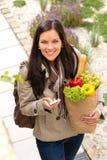 Lycklig kvinnashopping ringer livsmedel som texting grönsaker Arkivfoto