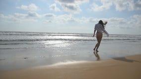 Lycklig kvinnaspring eller jogga på stranden nära havet Ung härlig flicka som tycker om liv och har gyckel på havet lager videofilmer