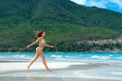 Lycklig kvinnaspring längs den vita stranden royaltyfria foton