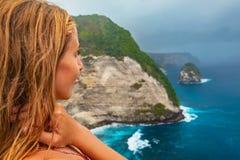 Lycklig kvinnaställning på den höga klippan under regnig himmel Arkivfoton