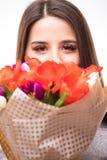 Lycklig kvinnastående med tulpan som isoleras på vit bakgrund 8 mars Arkivfoto