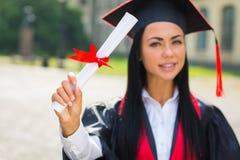 Lycklig kvinnastående på hennes le för avläggande av examendag Arkivbilder