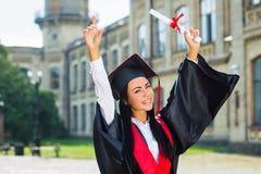 Lycklig kvinnastående på hennes le för avläggande av examendag Arkivfoton