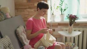 Lycklig kvinnastickaull på bakgrundsfönster i rum lager videofilmer