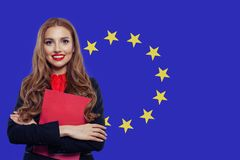 Lycklig kvinnastudent med boken mot bakgrunden f?r flagga f?r europeisk union royaltyfria foton
