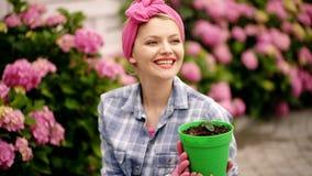 lycklig kvinnatr?dg?rdsm?stare med blommor Omsorg och bevattna f?r blomma jorder och g?dningsmedel kvinnaomsorg av blommor i tr?d lager videofilmer