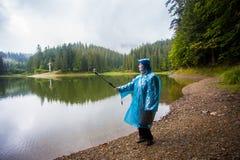 Lycklig kvinnaturist 60 gamla år i regnrocken som tycker om härlig sikt av den stora bergsjön Arkivbild