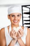 Lycklig kvinnlig bagareHolding Heart Shape deg Arkivfoton