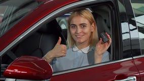 Lycklig kvinnlig chaufför som visar upp hennes biltangenter och tummar fotografering för bildbyråer