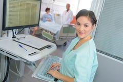 Lycklig kvinnlig doktor på datoren i sjukhusrum arkivbild