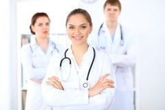 Lycklig kvinnlig doktor som håller den medicinska skrivplattan, medan den medicinska personalen är på bakgrunden Royaltyfri Bild