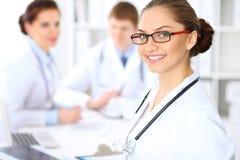 Lycklig kvinnlig doktor som håller den medicinska skrivplattan, medan den medicinska personalen är på bakgrunden Arkivbild