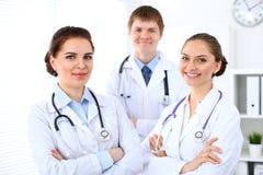 Lycklig kvinnlig doktor som håller den medicinska skrivplattan, medan den medicinska personalen är på bakgrunden Arkivfoto