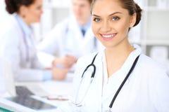 Lycklig kvinnlig doktor som håller den medicinska skrivplattan, medan den medicinska personalen är på bakgrunden Royaltyfri Fotografi