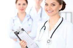 Lycklig kvinnlig doktor som håller den medicinska skrivplattan, medan den medicinska personalen är på bakgrunden Arkivbilder