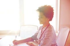 Lycklig kvinnlig doktors- eller sjuksköterskahandstil på sjukhuset Royaltyfri Bild