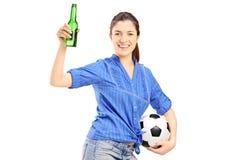 Lycklig kvinnlig fan som rymmer en ölflaska och en soccerball Arkivfoto