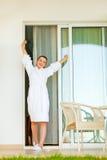 Lycklig kvinnlig i badrocken som sträcker, når att ha sovat royaltyfria foton