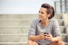 Lycklig kvinnlig idrottsman nen Listening till musik, medan vila royaltyfri bild