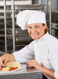 Lycklig kvinnlig Garnishing Dish Arkivbilder