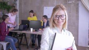 Lycklig kvinnlig kontorsarbetare i exponeringsglas som gör anmärkningar på papper och ler därefter på kameran arkivfilmer