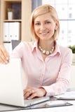 Lycklig kvinnlig kontorsarbetare med bärbar datordatoren Royaltyfri Bild