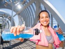 Lycklig kvinnlig löpare med driftiga drinkar för hydration Royaltyfri Bild