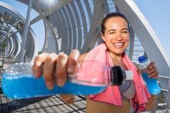 Lycklig kvinnlig löpare med driftiga drinkar för hydration Royaltyfri Foto