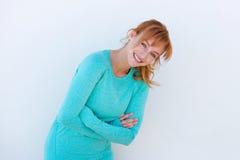 Lycklig kvinnlig löpare som skrattar mot den vita väggen royaltyfri foto