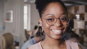 Lycklig kvinnlig ledare för nätt ung afrikansk amerikan i exponeringsglas som ler på kameran i modern kontorsCo-arbete bakgrund 4