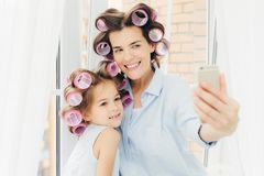 Lycklig kvinnlig moder och hennes småbarn med hårrullar på huvudet, po royaltyfri fotografi