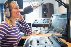 Lycklig kvinnlig radiovärdsradioutsändning i studio Royaltyfri Foto