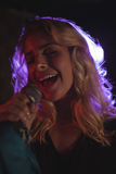Lycklig kvinnlig sångare som utför i upplyst nattklubb Royaltyfria Bilder