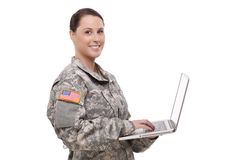 Lycklig kvinnlig soldat som använder bärbara datorn Arkivfoto