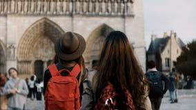 Lycklig kvinnlig som två går med röda ryggsäckar nära Notre Dame, den berömda domkyrkan eller kyrkan i Paris, Frankrike lager videofilmer